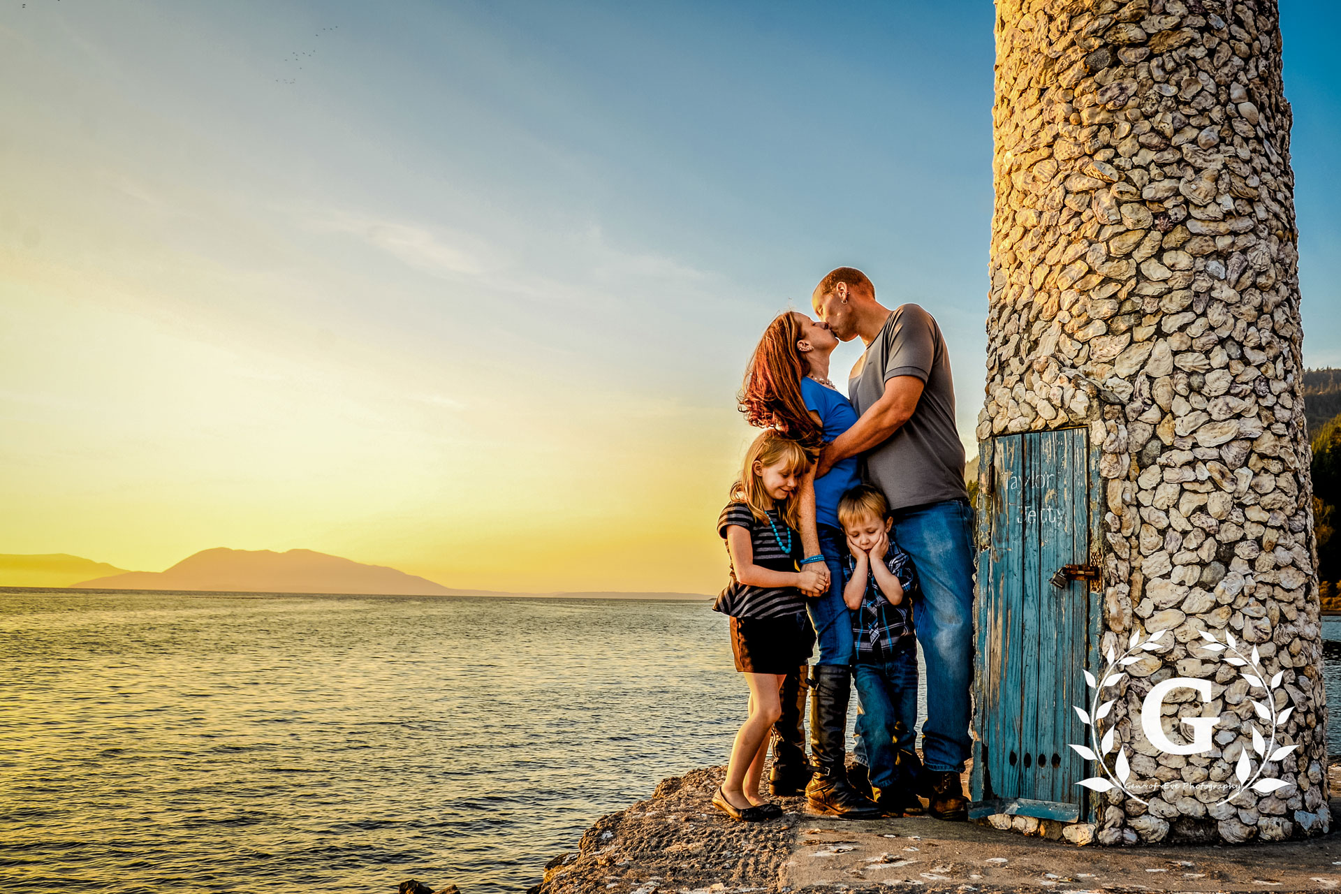 a family standing next to a lighthouse in front of the ocean